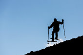 The silhouette of a freestyle skier jumping from the top of a peak of Vitosha mountain. He is participating in an freestyle competition of skiers and snowboarders during the weekend.