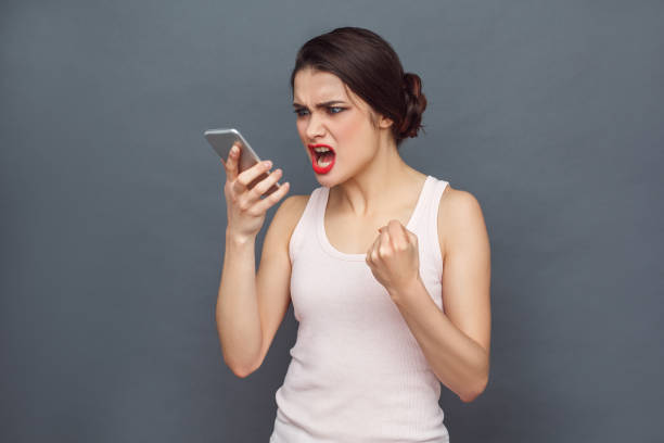 Freestyle. Woman standing isolated on grey shouting at caller on smartphone furious stock photo