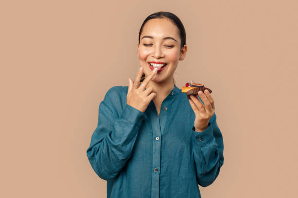 Freestyle. Young woman in denim dress standing isolated on bage holding fruit tart tasting laughing cheerful stock photo
