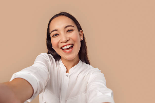 Freestyle. Young woman in shirt standing isolated on bage taking selfie taking selfie on smartphone laughing happy close-up stock photo