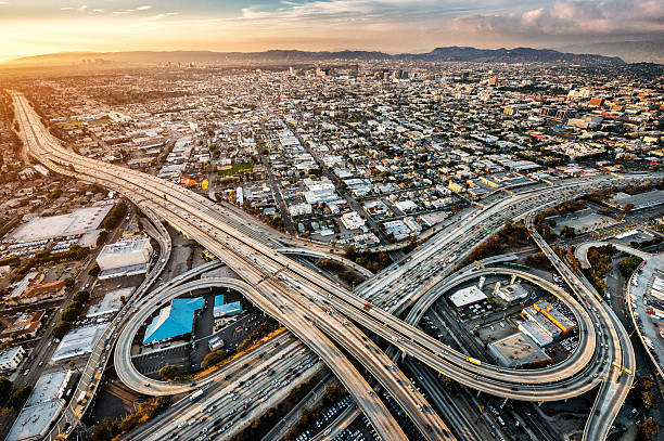 Freeway interchanges at dusk Helicopter point of view of Los Angeles highway interchanges at golden hour. Many details are visible in the image. overpass road stock pictures, royalty-free photos & images