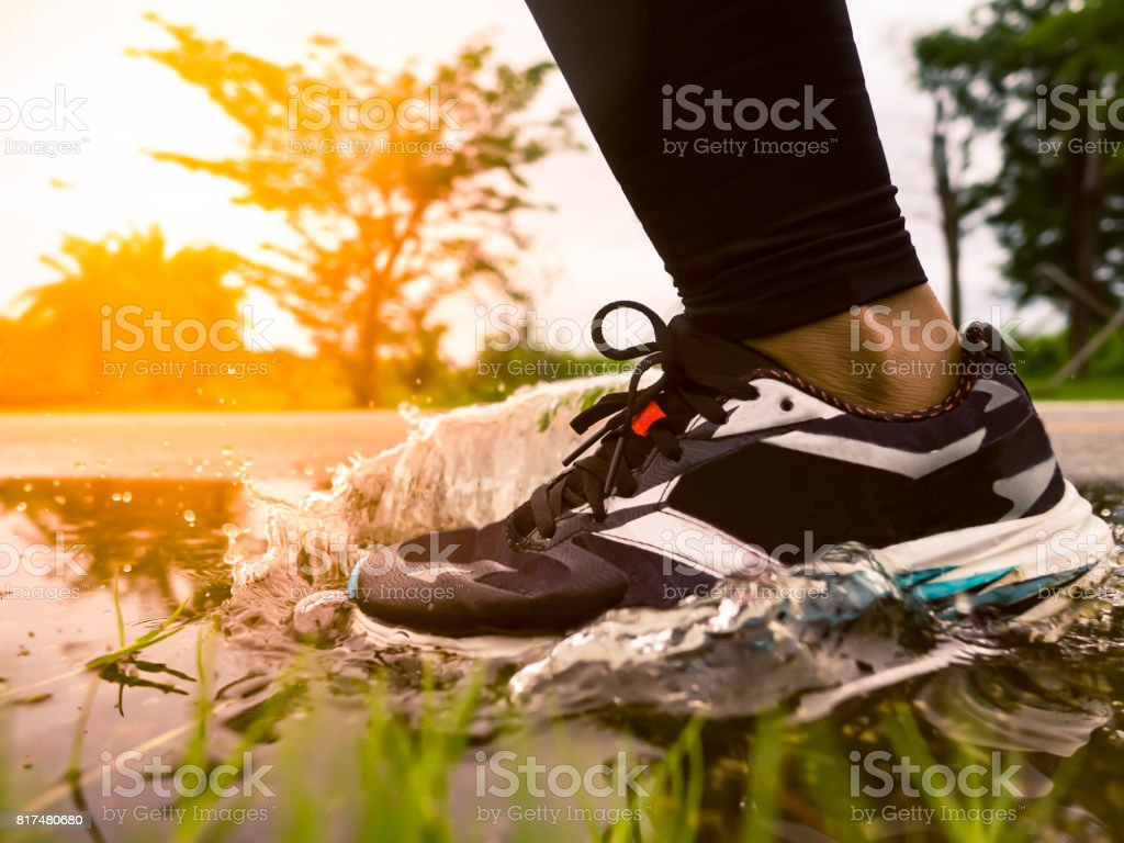 Freeze action of athlete's legs and running shoes splashing water after heavy rain stock photo