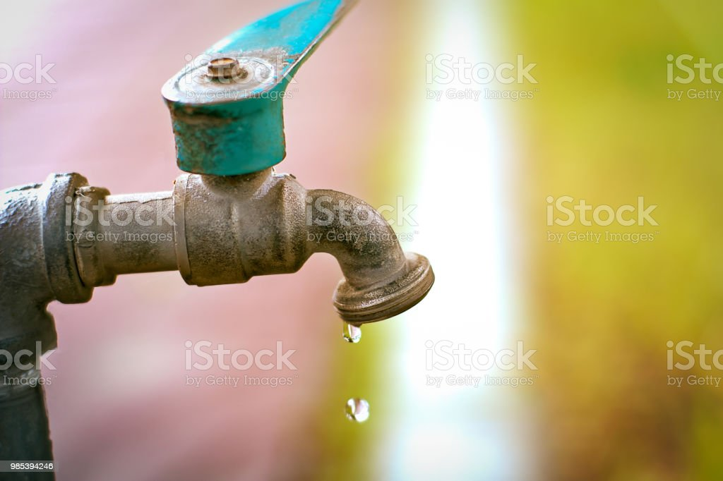 Freeze action tap water drops from water valve on a pathway in backyard with sunset nature background for environment, safe water concept stock photo