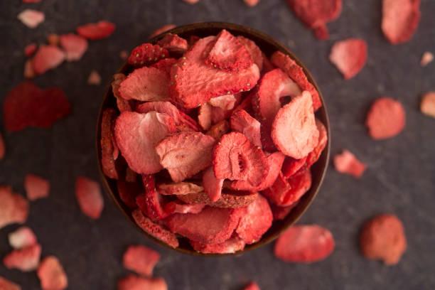 bevriezen van gedroogde aardbeien op een leisteen teller - gedroogd voedsel stockfoto's en -beelden