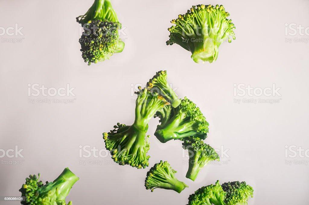 Freeze Dropping Green Brocolli on White Background stock photo