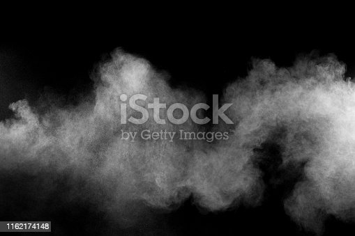 istock Freeze motion explosion of white dust on a black background. By throwing talcum powder out of hand. Stopping the movement of white powder on dark background. 1162174148