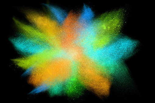 Freeze motion of colorful powder exploding, isolated on black, dark background. Abstract design of dust cloud. Particles explosion, screen saver wallpaper with copy space. Vivid green orange blue ash