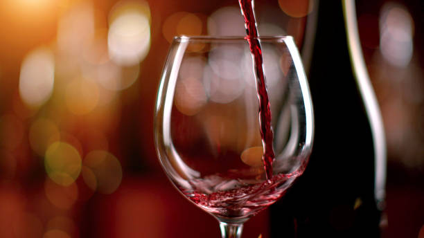 Freeze motion of pouring red wine into goblet Freeze motion of pouring red wine from bottle into goblet. Low depth of focus winetasting stock pictures, royalty-free photos & images