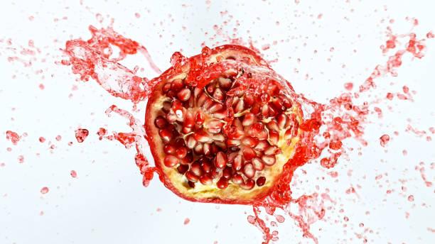 Freeze motion of sliced pomegranate with splashing juice. stock photo
