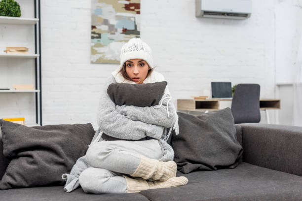 freezed young woman in warm clothes sitting on couch and hugging cushion at home freezed young woman in warm clothes sitting on couch and hugging cushion at home warm clothing stock pictures, royalty-free photos & images
