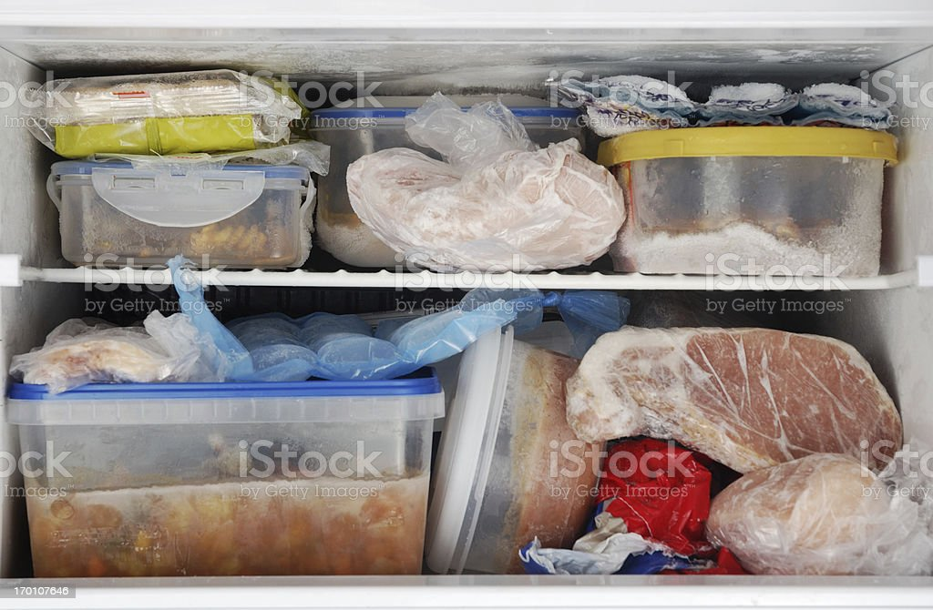 Freezer Frozen food inside a freezer. Lots of leftovers in plastic containers. Cold Temperature Stock Photo