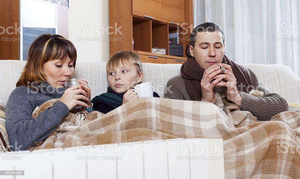 Congelación familia de tres temperaturas cerca de cálida radiador foto de stock libre de derechos