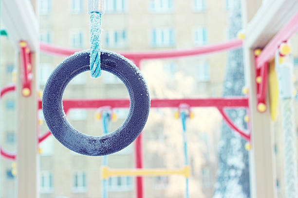 Freezing gymnastic rings. Snowy playground. Frost. stock photo
