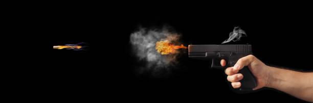 Freezing shot of a gun on a dark background. Concept gun club, gun-shop, shooting range. concept of freezing shot of a gun on a dark background . Concept gun club, gun-shop, shooting range. gun shop stock pictures, royalty-free photos & images
