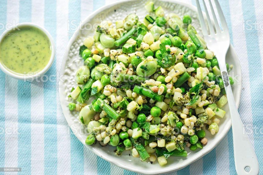 Fregola pasta & greens salad. Courgette, green beans, toasted fregola pasta with lemon & parsley dressing. stock photo