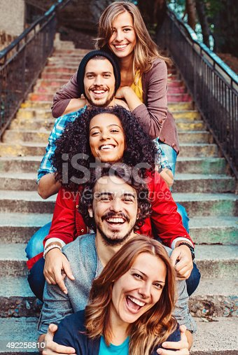 Mixed race young people laughing outdoors