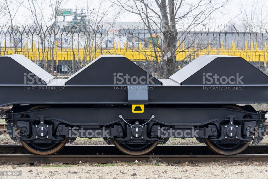 Freight (cargo) train - black cars (wagons). Details.New 6-axled flat wagon stock photo