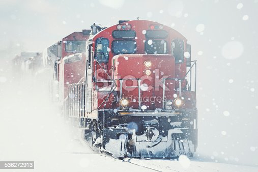 A freight train charges through heavy snow.  Slight cross processing.