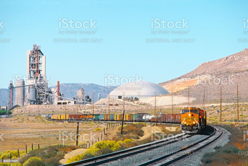 BNSF freight train passing industrial cement factory in California stock photo