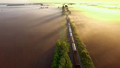 Freight train rolls across surreal, foggy landscape at sunrise, aerial view.