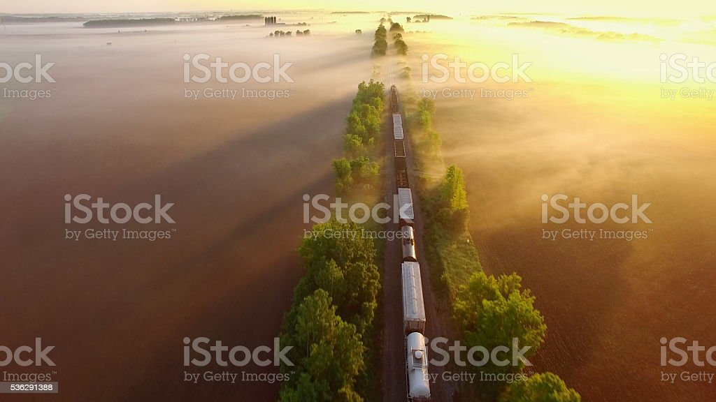 Freight train rolls through fog, across breathtaking landscape at sunrise. stock photo