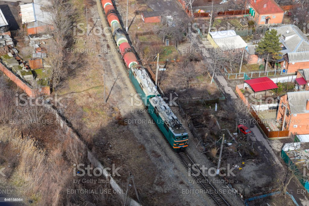 Freight train traveling through the city buildings. stock photo