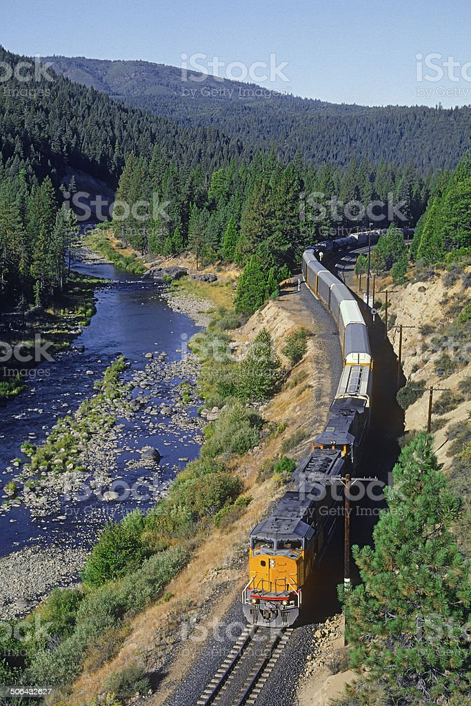Freight (cargo) train winding along a scenic river valley stock photo