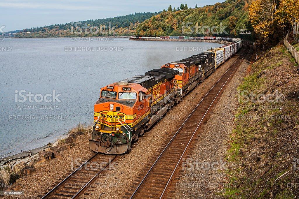 Freight train winding along Puget Sound near Seattle, WA stock photo