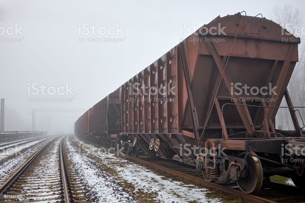 Freight train with hopper cars in the fog stock photo