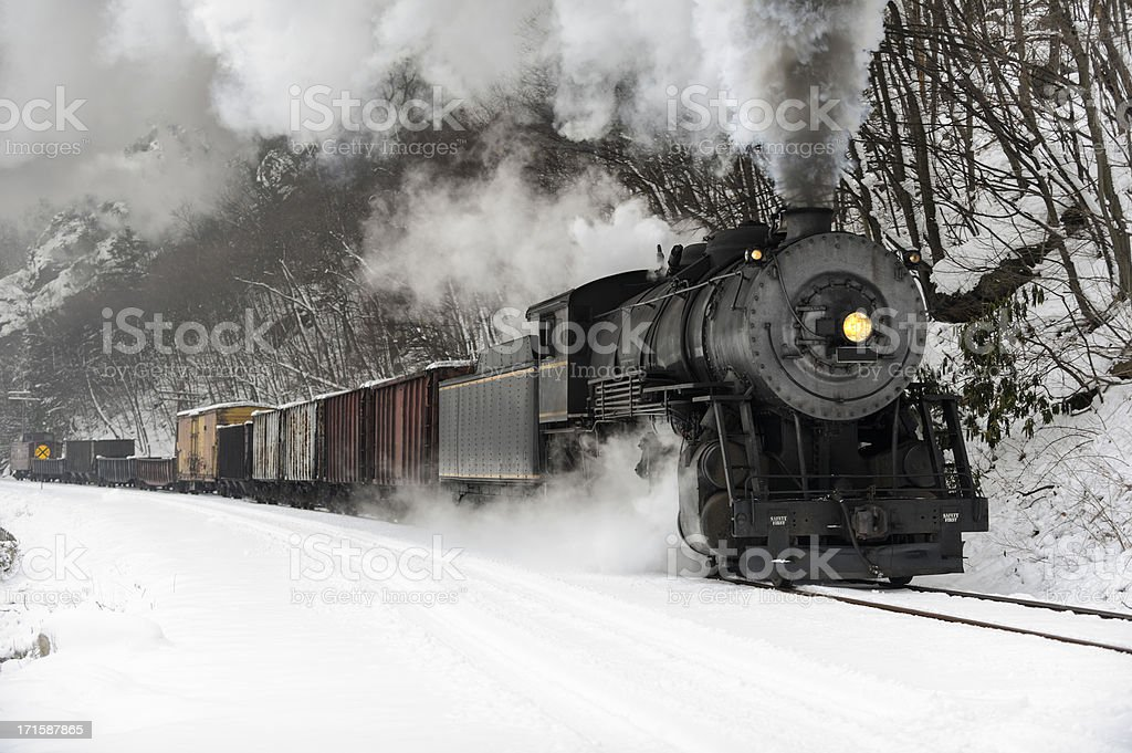 Freight Train with Steam Locomotive Smoke in Cold Winter Snow stock photo