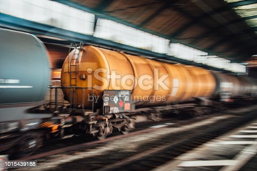 Freight train with tanks in motion crossing a railroad station