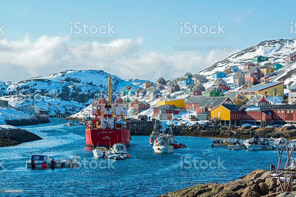 Freight vessel approaching a small harbour in Greenland stock photo