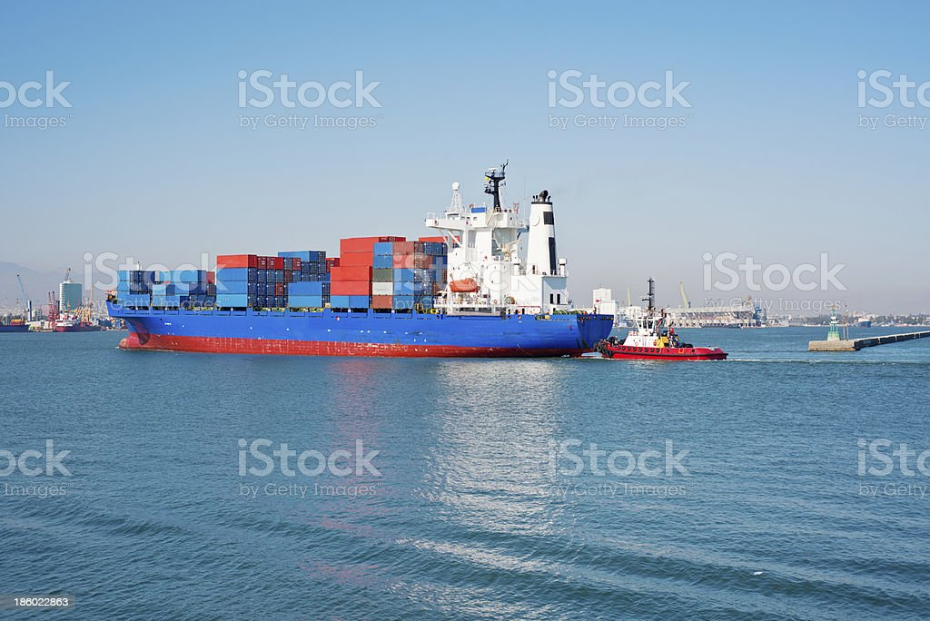 Freighter being guided into port by tug. royalty-free stock photo