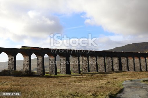 Powerful Diesel Freight Train hauls wagons of timber across the exposed Ribblehead Viaduct in Yorkshire, UK