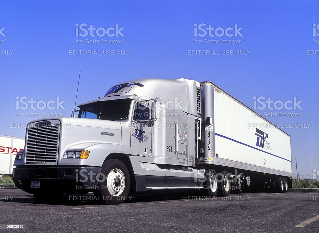 Freightliner semi-truck and trailer in parking lot stock photo