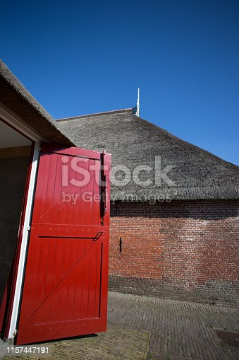 Freisland, Netherlands: Red Barn Door (Close-Up), Blue Sky, Thatched Roof. Some copy space available in the sky.