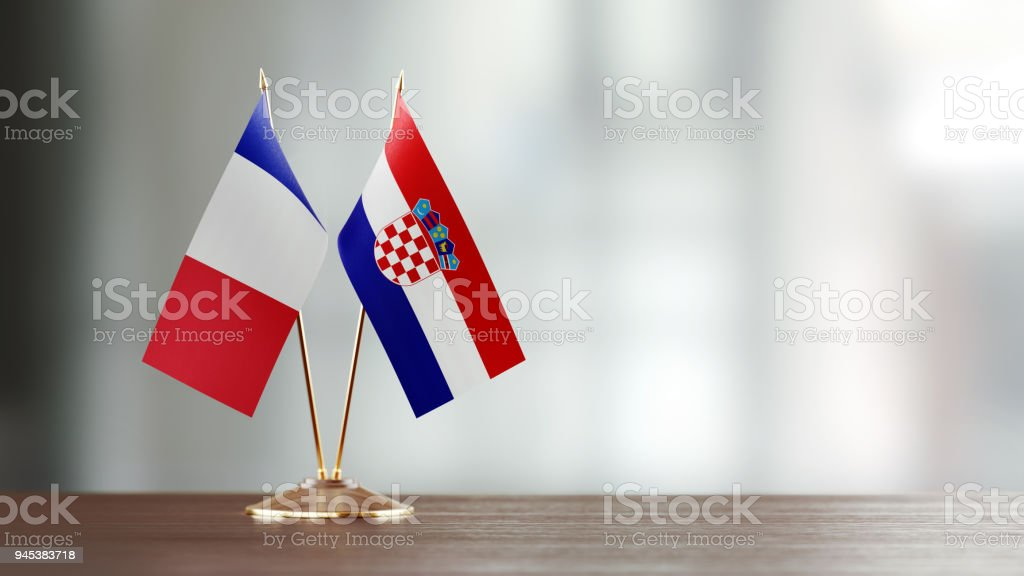 French And Croatian Flag Pair On A Desk Over Defocused Background - foto stock