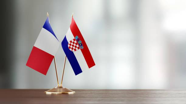 Par de pavilhão francês e croata em uma mesa sobre fundo desfocado - foto de acervo