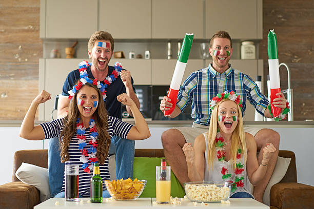 french and italian soccer fans watching tv stock photo