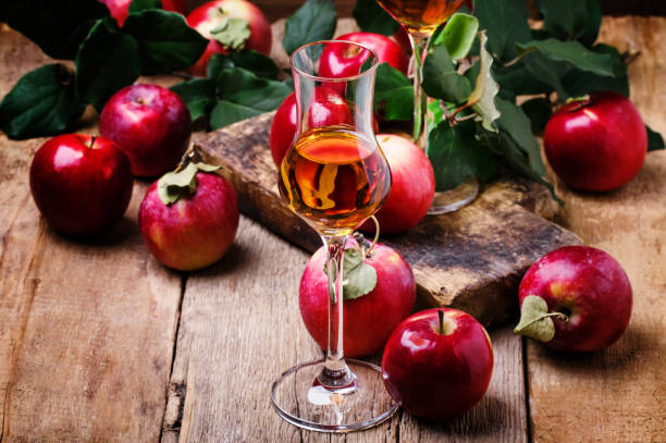 French apple strong alcoholic drink, still life in rustic style French apple strong alcoholic drink, still life in rustic style, vintage wooden background, selective focus calvados stock pictures, royalty-free photos & images
