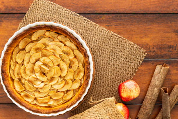 French apple tart aside Gala apples and cinnamon sticks on a jute or burlap mat on a vintage wood table. Flat lay. Top view. Copy space. stock photo