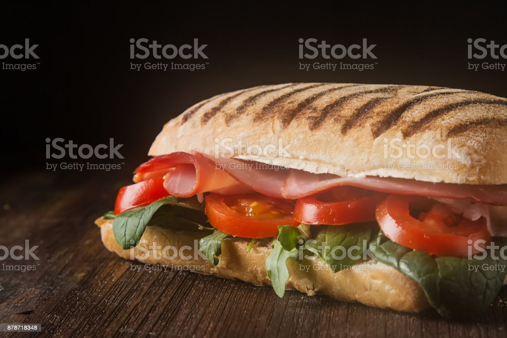 French baguette with sausage, tomatoes and lettuce. Dark background.