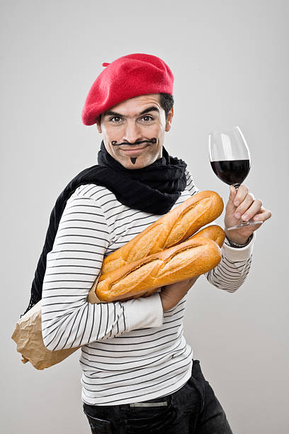 French Baguettes And Wine A French man in a red beret carrying French baguettes and holding a glass of red wine. french culture stock pictures, royalty-free photos & images