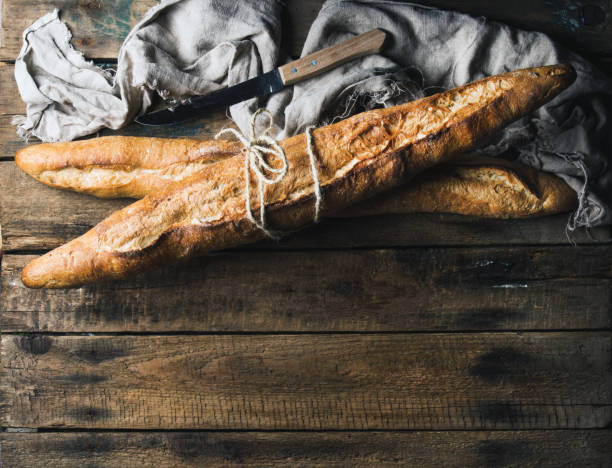 French baguettes on rough rustic wooden background stock photo