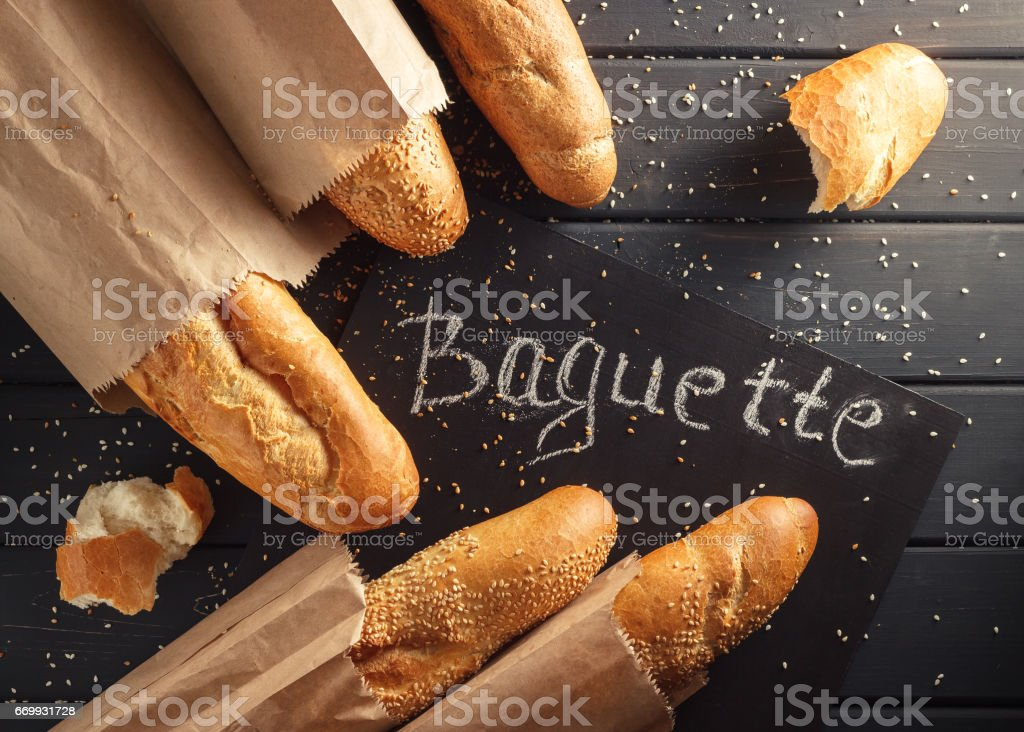 French baguettes with sesame seed on black wooden background stock photo