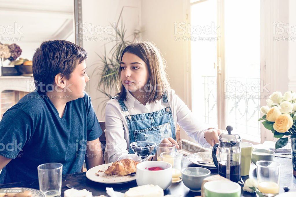 french boy and teenage girl looking eachother at breakfast table stock photo