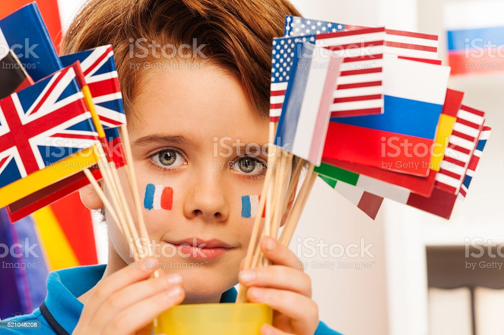 French boy with flag on cheeks hide behind banners stock photo