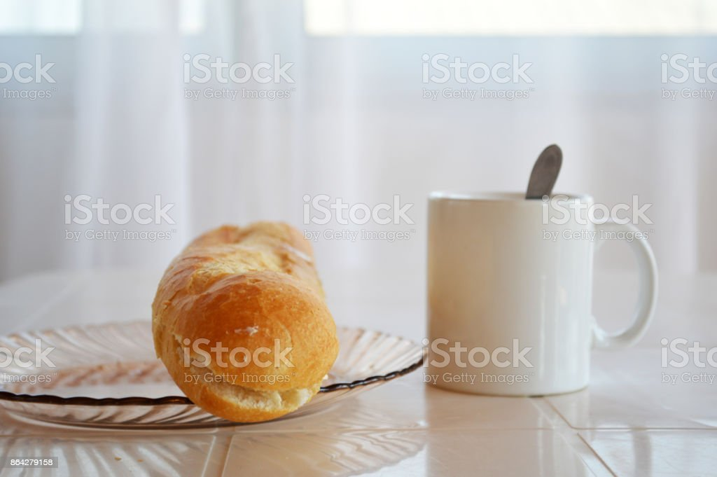French breakfast : Milk tea in a white cup with french bread royalty-free stock photo