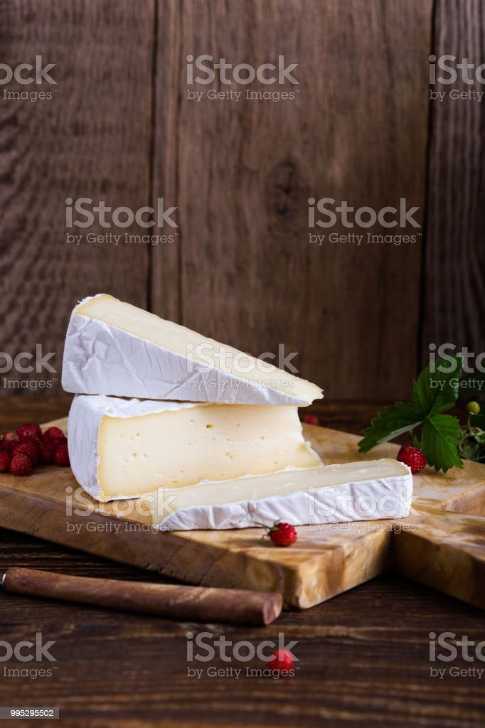 French brie cheese, wild strawberries and white purple wild flower bouquet stock photo