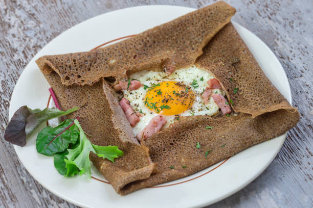 french Buckwheat crepe galette with bacon and egg for tasty healthy lunch on grey wooden background stock photo